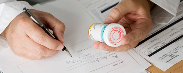A close-up of a male doctor's hands writing a prescription while inspecting the label of a bottle of medication, illustrating how behavioural science can impact healthcare provider behaviour